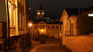 Vy mot rådhuset i Borgå. Gamla trähus kantar en kullerstensgata som leder ut på ett kullerstensbelagt torg. På andra sidan torget står ett stort hus med ett upplyst klocktorn. Det är mörkt men vyn lyses upp av lampor och julljus.