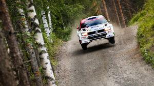 En rallybil susar fram på en grusväg.