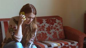 Nainen puhuu puhelimessa sohvalla.