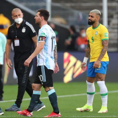 Argentinas tränare Lionel Scaloni och storstjärnan Lionel Messi lämnar planen efter att matchen stoppats.
