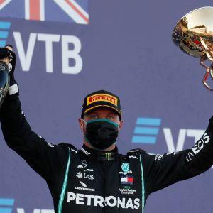 Valtteri Bottas lyfter champagne och pokal upp mot skyn.