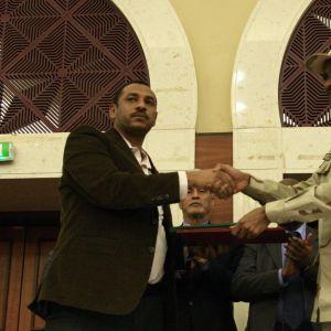 Representanter för militärjuntan och proteströrelsen skakar hand
