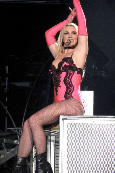 Britney Spears sitter på en pall och dansar och sjunger medan hon uppträder på scen i London år 2011.