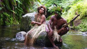 Wawa (Marie Wawa) och Dain (Mungau Dain) sitter tillsammans på en sten i en bäck.