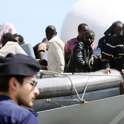Båtflyktingar räddas av italienska sjöbevakningen