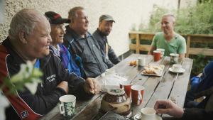 Grupp med män dricker kaffe vid ett terassbord.
