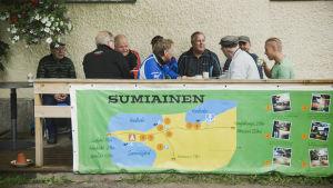 Ryhmä miehiä juo kahvia ja juttelee ulkoterassilla. Terassin kaiteeseen kiinnitetty kartta Sumiaisten kylästä.