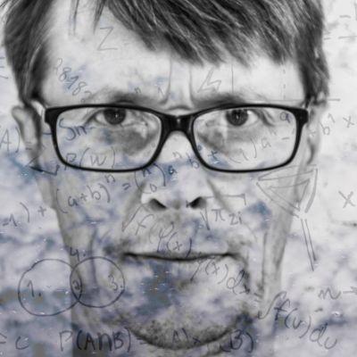 Arto Ranta-Ylitalo katsoo vakavasti kameraan, taustalla kaavoja, jotka luovat mielikuvaa keksijästä.