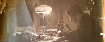 En hundra år gammal bild av en man som sitter och skriver vid sitt arbetsbord.