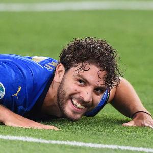 Manuel Locatelli ligger på gräset med ett leende på läpparna.