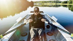Sam Öhman soutaa veneessä.