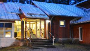 Ingången till ett rött trähus. Det är mörkt ute men inifrån kommer ett varmt sken. På glasdörrarna har man limmat fast pappfigurer föreställande tomtar.