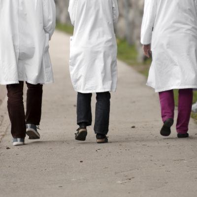 Tre läkare promenerar på gatan.