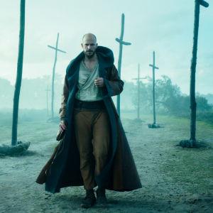 Svenska skådespelaren Gustaf Skarsgård spelar trollkarlen Merlin i tv-serien Merlin. Här ser man honom gå i ett disigt mörkt landskap där flera träkors syns.