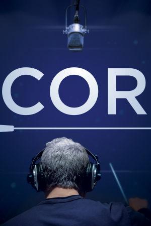 Kapellimestari johtaa selin luurin päässä. Julistekuva dokumenttielokuvaan Score.