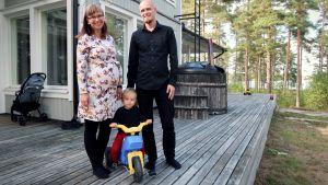 Richard och Pipsa Palonen står på sin terrass med sin tvååring.