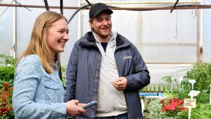 Stella Törnroth med partnern Jonas Bergström i ett växthus omgivna av grönt och blommor.
