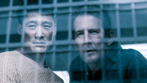 Poliserna Alf och Mads tittar ut genom ett fönster föresett med galler.