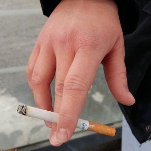 En hand som håller i en cigarett mellan pek- och långfingret.