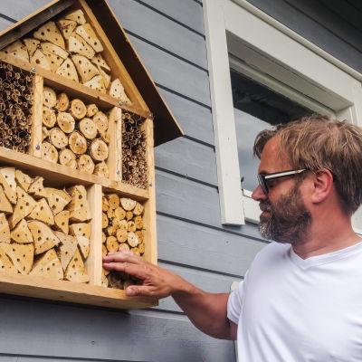En man i vit t-skjorta och solglasögon står invid en grå husvägg. På väggen hänger ett insektshotell i trä. Det ser ut som en låda fylld med träklabbar som har hål i sig.