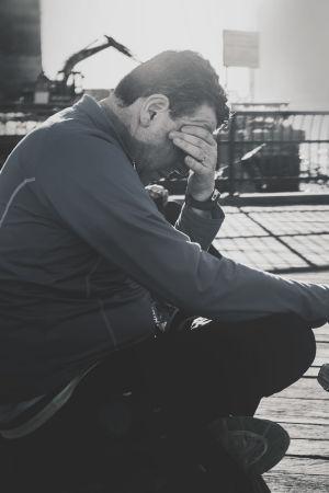 En medelålders man sitter ute i en hamn