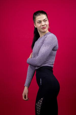 Fitness-urheilija Pernilla Böckerman poseeraa kameralle punaista taustaa vasten.