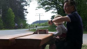 Tränaren Bennie Lindberg sitter på en bänk och följer med när de han tränar åker förbi på cykel