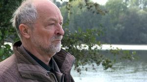 En man står i profil, han är gråhårig och har skägg. I bakgrunden syns landskap.