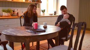 Henrika och Mathias Gustafsson sitter i ett mysigt, grönt kök med sin son i famnen vid köksbordet.