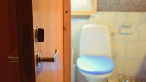 En gammal toalett med uppriven vägg och isoleringen framme..