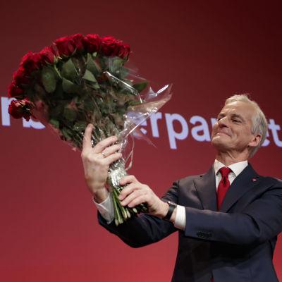 En man i grått hår håller i en bukett med röda rosor och ler.