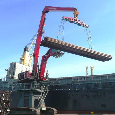 Kran lyfter virke från skepp i Lovisa hamn.