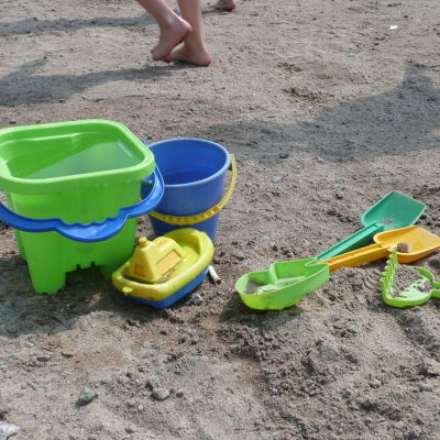 Flera plastleksaker i olika färger på en sandstrand