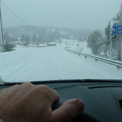 Hand som håller i bilens ratt, snöig väg.