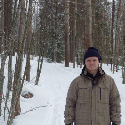 Mies seisoo talvisen ulkoilureitin varrella.