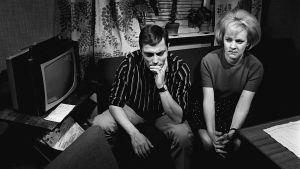 Heikki ja Kaija istuvat sohvalla murheissaan. Mustavalkoinen kuva.