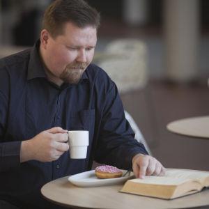 Kaiken voi lukea -blogin kirjoittaja lukee kirjaa ja juo kahvia