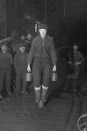 En man lyfter två tunga lod. Bilden är tagen 1936 i Strömfors bruk.