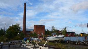 I bakgrunden synns ett stort tegelhus med en hög skorsten. I förgrunden syns en båt, båttrailrar och lite bråte.