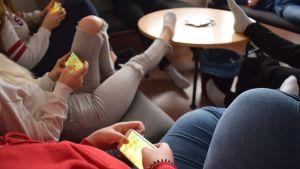 Ungdomar sitter med mobiler i handen.