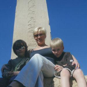 Helena Ahti-Halberg Egyptin-lomakuvassa taustallaan obeliski ja kainaloissaan lapsensa Anton ja Emil pikkupoikina.