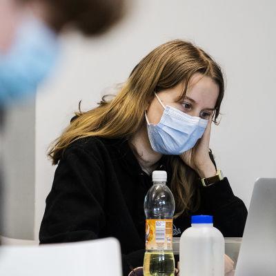 En ung kvinna i munskydd sitter vid en pulpet framför en dator.
