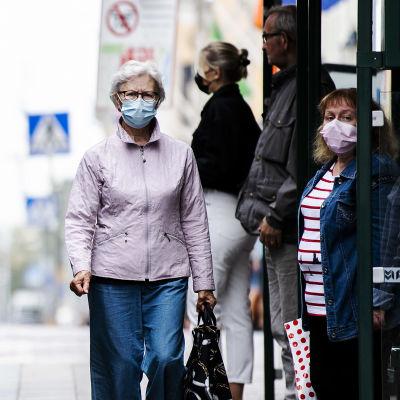 Människor går förbi en spårvagn på Alexandersgatan i Helsingfors. De har munskydd på sig.