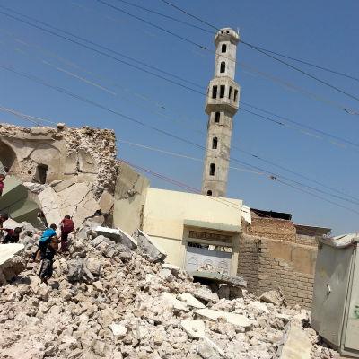 Pojkar som klättrar på en ruinhög i den irakiska staden Mosul. Ruinerna är en av IS förstörd grav.