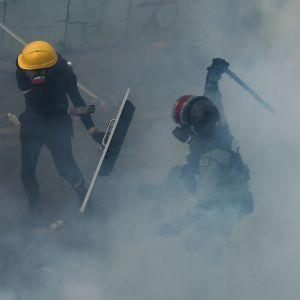 Demonstrant blir slagen av kravallpolis under sitt försök att hitta en trygg passage ut från universitetet 18.11.2019