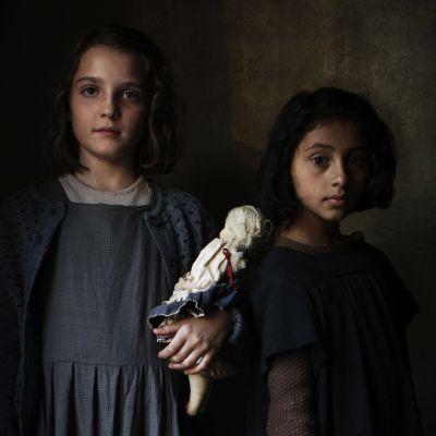 Kaksi tyttöä tummaa taustaa vasten, katsovat kameraan.