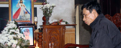 En sörjande medelålders man tittar på ett foto av en ung man. Framför fotot brinner ett ljus. På väggen hänger en bild av Jesus.
