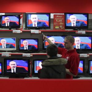 En elektronik affär i Ryssland med TV apparater som visar Vladimir Putin.
