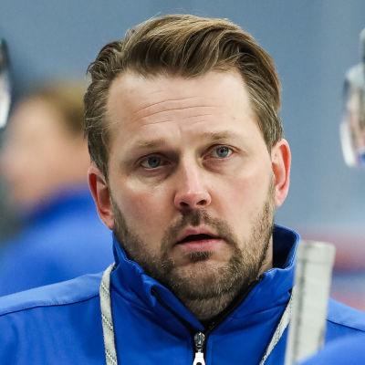 Antti Pennanen tittar allvarligt mellan två spelare.
