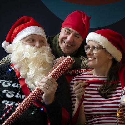 Kike är utklädd till jultomten som delar ut gåvor till Jens och Jenny prydda i tomteluvor.